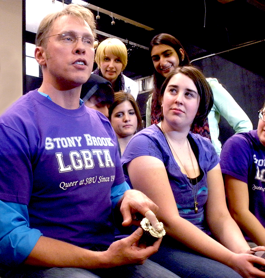 Sex and relationship educator Reid Mihalko of ReidAboutSex.com wearing a purple Stony Brook LGBTA t-shirt sitting with Stony Brook College students teaching a safer sex demonstration on a cupcake wearing a finger cot