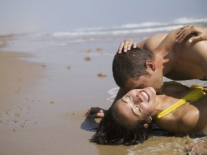 A man and a woman in the surf on the beach kissing