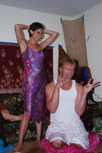 Sex educator Reid Mihalko wearing a white tanktop and sarong makes a goofy face with Kamala Devi laughing behind him