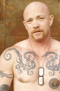 Head and shoulders photo of sex educator and transexual adult performer Buck Angel wearing military dog tags and no shirt, showing off his tatoos