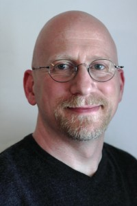 Close up photo of sex educator Charlie Glickman wearing a black tshirt and glasses