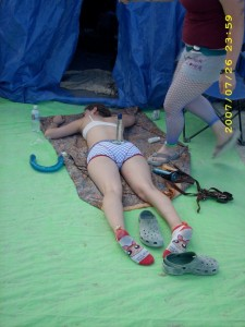 An exhausted Camp Beaverton woman asleep in front of the Beaver Den at Burning Man with a dildo balanced on her butt and several others strewn around her