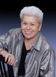 sex educator and grandmother of female masturbation, Betty Dodson, smiling and wearing a silver jacket to match her silver hair.