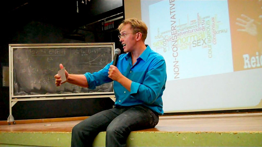 Sex and relationship expert Reid Mihalko in a blue, button up shirt, sitting on an auditorium stage with hand held mic and note cards, lecturing with a slide show on the projector screen behind him