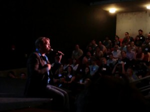 Sex and relationship expert Reid Mihalko of ReidAboutSex.com sitting on a dark stage in a dark suit and blue shirt speaking to a full house at a MindshareLA event