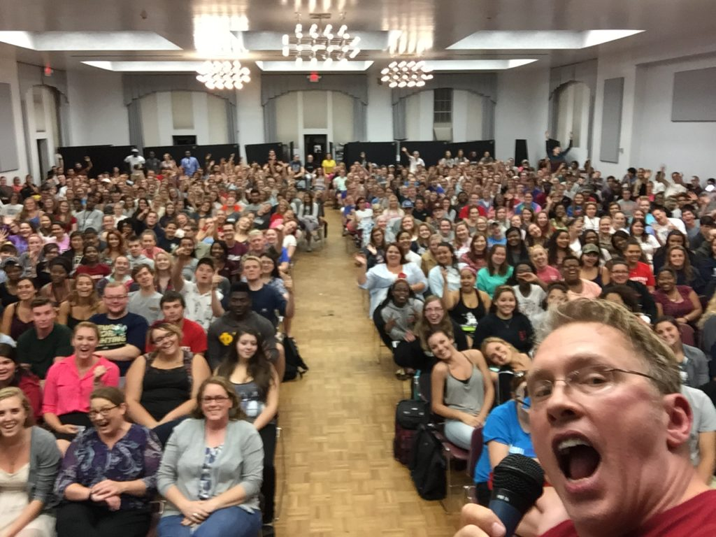 """Sex and relationship educator Reid Mihalko of ReidAboutSex.com making a silly face while taking a selfie of the Lynchburg College auditorium's packed house of cheering students before his sexual assault prevention talk entitled """"How To Be a Gentleman and Still Get Laid."""""""