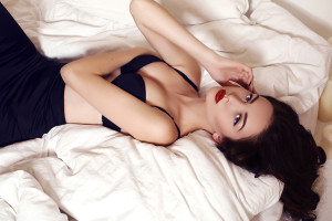 Beautiful Woman With Long Dark Hair Lying On Bed In Bedroom
