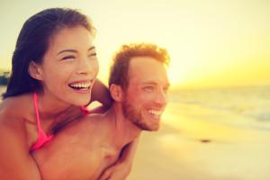 Happy beach fun multicultural couple - summer love in sunset. Yo