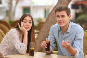 Man and woman dating in a restaurant terrace but she is boring while he speaks