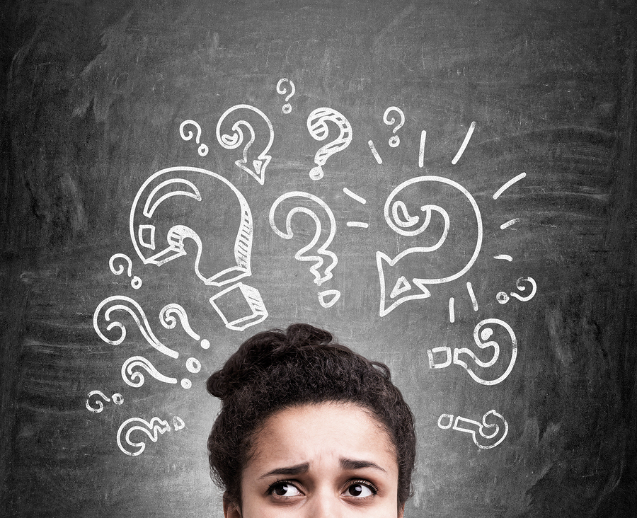Confused african american woman thinking about answers to her questions on chalkboard background