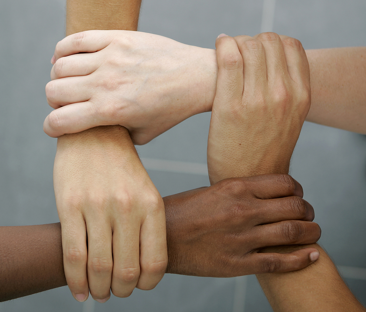 Four hands of people of varying skin tones joining together by holding onto the wrist of the hand in front of it.