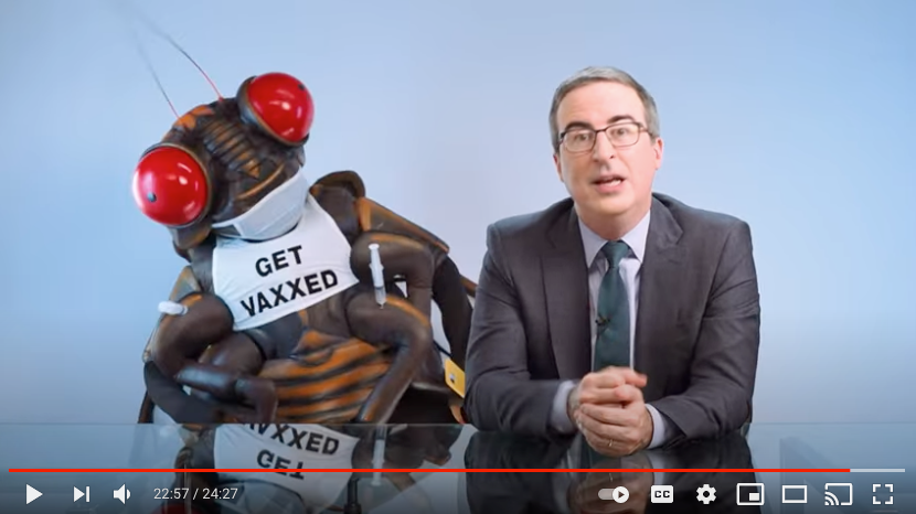 """Screenshot from Youtube of John Oliver on LaastWeekToinght sitting next to a giant mascot costumed person dressed up as a cicada with a tshirt that says, """"Get Vaxxed"""""""