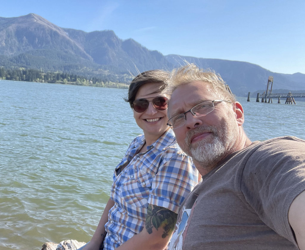 Selfie of a smiling Allison Moon, a white woman with short auburn hair wearing a blue, white and orange checkered shirt and sunglasses, and Reid Mihalko, a blonde, grey bearded, eyeglass-wearing white guy in his 50s, sitting by a rivers edge on a sunny day with the Oregon Gorge in the background