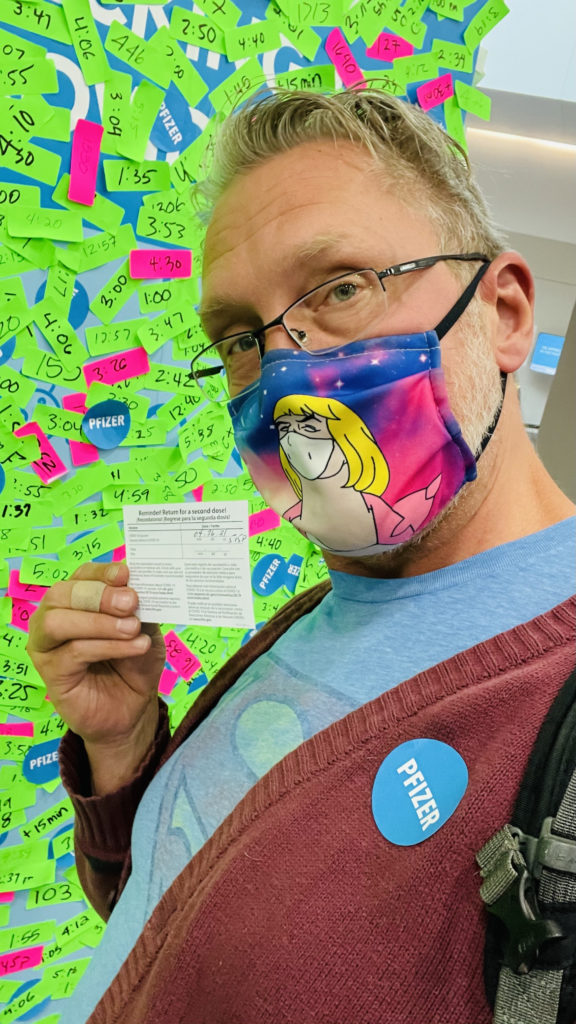 Image of a blonde, white man wearing eyeglasses and a colorful a He-Man meme printed cloth COVID mask holding up his vaccination card and wearing a blue Pfizer sticker on his burgundy sweater